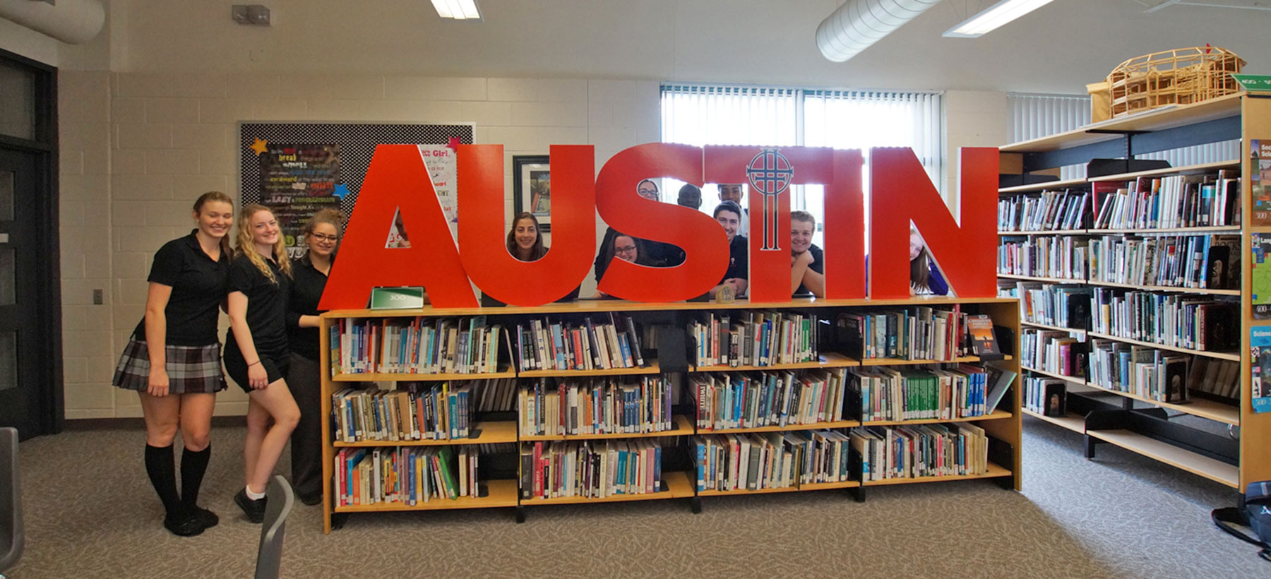 Students standing behind Austin sign - peaking through letters