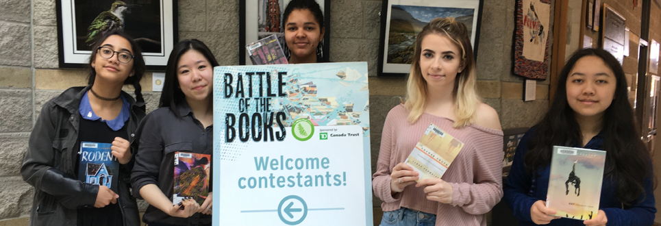 Five female students holding Battle of the Books sign and their books