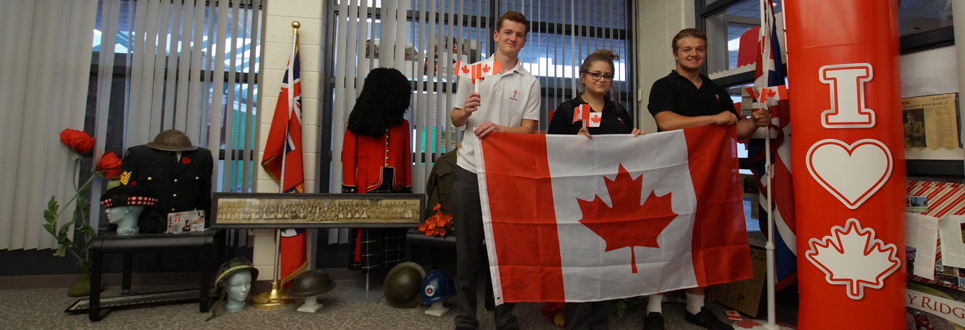 Students holding Canadian flag standing by World War display