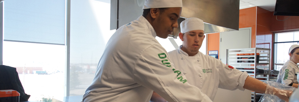 Two male students in chef outfits in a kitchen