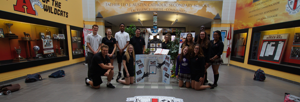 Students standing by cross in front lobby of high school